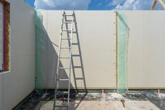 Construction of new and modern modular house. Construction new and modern modular house from composite sip panels. Metal ladder standing by the wall in empty stock images