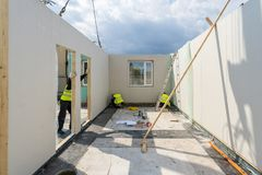 Construction of new and modern modular house. Process of construction new and modern modular house from composite sip panels. Three builder man in uniform wear royalty free stock photography