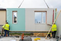 Construction of new and modern modular house. Process of construction new and modern modular house from composite sip panels. Three workman in special protective stock photo