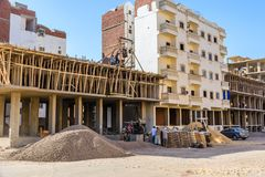 Construction of the new modern residential building, workers pour concrete in wooden framework. Hurghada, Egypt. Hurghada, Egypt - December 6, 2018: Construction royalty free stock photography