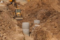 Construction of a new sewerage system. The bulldozer digs a trench for sewer pipes. Construction works. Stock Photography