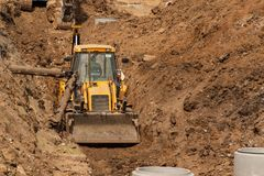Construction of a new sewerage system. The bulldozer digs a trench for sewer pipes. Construction works. Stock Photo