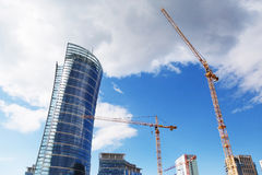 Construction of a new skyscraper of glass and concrete. Bottom view of the building and the tower crane Royalty Free Stock Photo