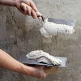 Construction notched trowel and worker hands Royalty Free Stock Images