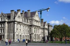 Construction is ongoing on college campuses. Stone buildings on the Trinity College campus in Dublin, Ireland stand before a construction crane. To keep up with stock images