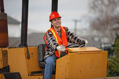 Construction operator. Smiling road construction worker behind construction roller's wheel royalty free stock photography