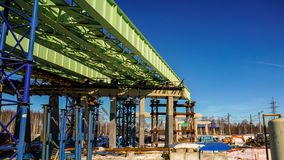 The construction of the overpass over the functioning railway. Temporary metal structures are gradually replaced by reinforced concrete pillars stock image