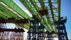 Construction of the overpass over the functioning railways and highways. Stacked metal structures spans over the road royalty free stock images