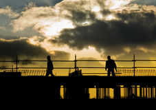 Construction people silhouette. Silhouette of construction workers on building site with dramatic cloudscape royalty free stock photo