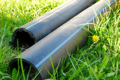 Construction pipes lying on the grass Stock Photo