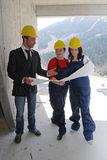 Construction plan. Boss holding construction plan and explaining it to two workers Royalty Free Stock Photos