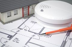 Smoke detector with a house and flames royalty free stock photography