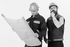 Construction plan concept. Architects in hard hat on thoughtful faces. Discuss drawing, plan, project. Men in helmets with blueprint on white background Royalty Free Stock Image