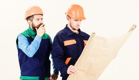 Construction plan concept. Architects in hard hat on thoughtful faces. Discuss drawing, plan, project. Builder, engineer, architect work on project. Men in stock photography