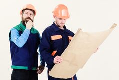 Construction plan concept. Architects in hard hat on thoughtful faces. Discuss drawing, plan, project. Men in helmets with blueprint on white background stock photo
