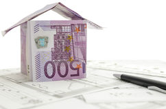 Construction plan with house made of money on it Stock Photos