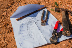 Construction plan and tools laid on the ground Royalty Free Stock Photos