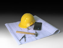 Construction planning on dark background. Hard hat, blueprints, hammer, calculator, calipher on dark gradient background Royalty Free Stock Image