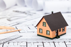Construction plans with drawing tools and House Miniature on blu Royalty Free Stock Image