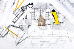 Construction plans with drawing Tools and House Miniature on blu Royalty Free Stock Photography