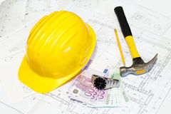 Construction plans and hard hat. In architecture time means money, a picture with some house plans and a pencil, hammer and yellow helmet. Construction plans and Stock Photos