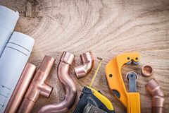 Construction plans measuring tape water pipe cutter connectors o. N wood board plumbing concept Royalty Free Stock Photos