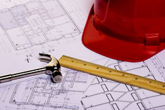 Construction plans with red helmet and drawing tools Royalty Free Stock Photos