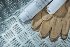 Construction plans safety gloves on channeled metal sheet.  royalty free stock images