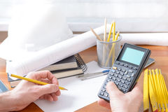 Construction plans and tools. Architect using engineering calculator at his work. Construction plans, blueprint, ruler and drawing tools Royalty Free Stock Photography