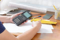 Construction plans and tools. Architect using engineering calculator at his work. Construction plans, blueprint, ruler and drawing tools Stock Photo