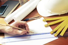 Construction plans and tools. Hand drawing with pencil using ruler, construction plans with helmet, measure, mobile phone, and drawing tools Stock Photo