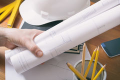 Construction plans and tools. Construction plans in hand with helmet, measure, mobile phone, and drawing tools Royalty Free Stock Photo