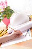 Construction plans and tools. Construction plans in hand with helmet, measure, mobile phone, and drawing tools Stock Photography