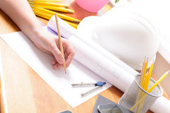 Construction plans and tools. Construction plans in hand with helmet, measure, mobile phone, and drawing tools Royalty Free Stock Image