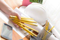 Construction plans and tools. Construction plans in hand with measure, mobile phone, and drawing tools, helmet Stock Photos