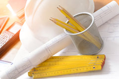 Construction plans and tools. Construction plans with helmet and drawing tools on blueprints with calculator in a background Stock Photo