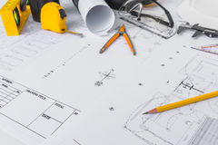 Construction plans with White helmet and drawing tools on bluepr Stock Photos
