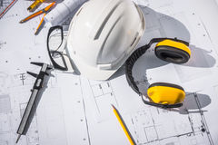 Construction plans with White helmet and drawing tools on bluepr Stock Image