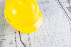 Construction plans with yellow helmet Stock Image
