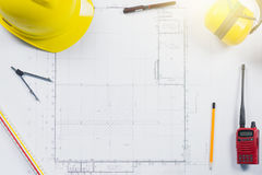 Construction plans with yellow helmet and drawing. Tools on blueprints at office stock photography