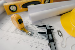 Construction plans with yellow helmet and drawing tools on bluep Royalty Free Stock Images