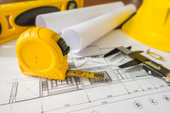 Construction plans with yellow helmet and drawing tools on bluep Stock Photos