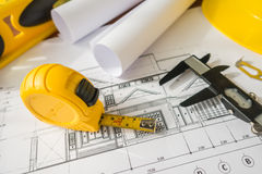 Construction plans with yellow helmet and drawing tools on bluep Stock Photo
