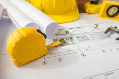 Construction plans with yellow helmet and drawing tools on bluep Royalty Free Stock Photos