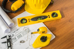 Construction plans with yellow helmet and drawing tools on bluep Royalty Free Stock Photo