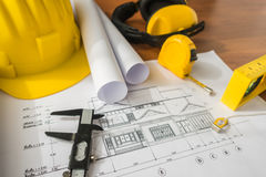 Construction plans with yellow helmet and drawing tools on bluep Stock Image
