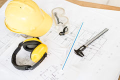 Construction plans. With yellow helmet and drawing tools on blueprints Royalty Free Stock Image