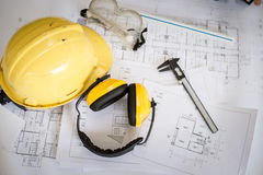 Construction plans. With yellow helmet and drawing tools on blueprints Royalty Free Stock Photo
