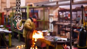 Construction plant. A big industrial lifting chain with a hook on the end. A man welding on the background. Mid shot stock image