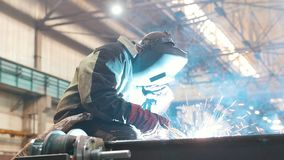 Construction plant. A man worker in a helmet using a welding machine on metal detail. Fire sparkles stock footage